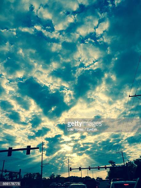 Cars Waiting At Stoplight Against Cloudy Sky
