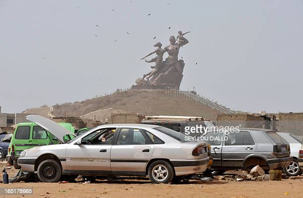 Cars waiting repair are seen in the foreground near the 'African Renaissance Monument' on April 1 2010 in Dakar during preparations for the April 3...
