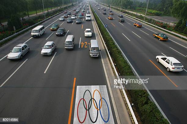 Cars without the required special permits drive in the lane next to the central fence, which is reserved as an Olympic lane, during morning rush hour...