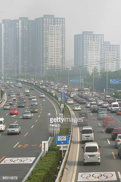 Cars without the required special permits drive in the lanes next to the central fence, which are reserved as Olympic lanes, during morning rush hour...
