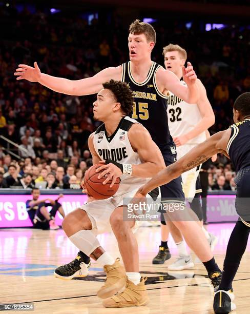 Carsen Edwards of the Purdue Boilermakers controls the ball against Jon Teske of the Michigan Wolverines during the championship game of the Big Ten...