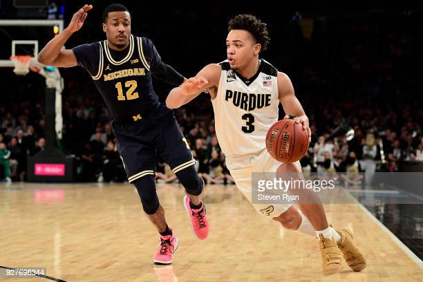 Carsen Edwards of the Purdue Boilermakers drives against MuhammadAli AbdurRahkman of the Michigan Wolverines during the championship game of the Big...