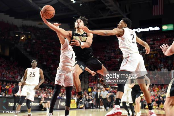 Carsen Edwards of the Purdue Boilermakers drives to the basket between Anthony Cowan Jr. #1 and Aaron Wiggins of the Maryland Terrapins during a...