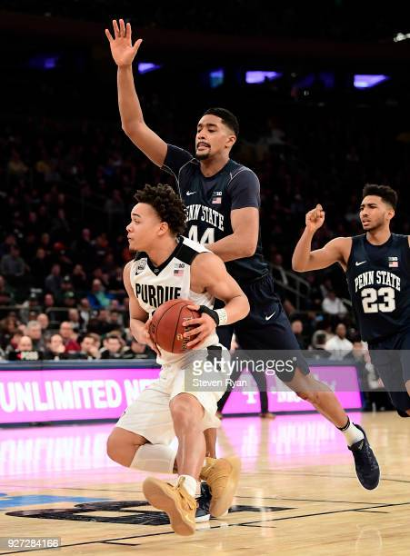 Carsen Edwards of the Purdue Boilermakers is defended by Julian Moore of the Penn State Nittany Lions during the semifinals of the Big Ten Basketball...