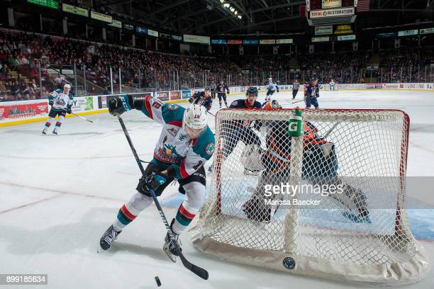 Carsen Twarynski of the Kelowna Rockets skates with the puck behind the net of Dylan Ferguson of the Kamloops Blazers during third peirod on December...