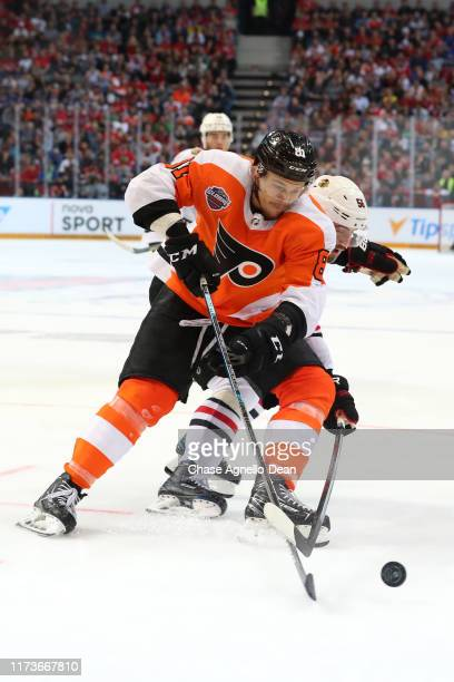 Carsen Twarynski of the Philadelphia Flyers and Erik Gustafsson of the Chicago Blackhawks chase the puck in the third period during the NHL Global...
