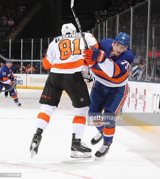 Carsen Twarynski of the Philadelphia Flyers hits Samuel Bolduc of the New York Islanders during the first period at the Nassau Veterans Memorial...