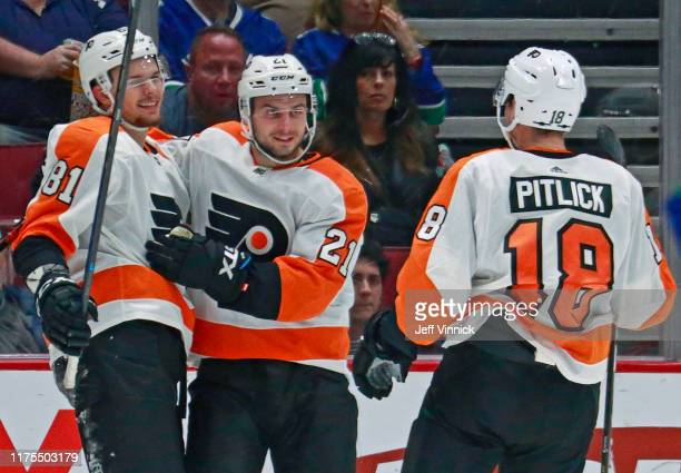 Carsen Twarynski of the Philadelphia Flyers is congratulated by teammates Scott Laughton and Tyler Pitlick after scoring during their NHL game...