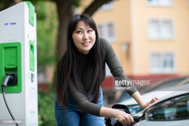 carsharing, woman charging an electric car - alternative fuel vehicle stock pictures, royalty-free photos & images
