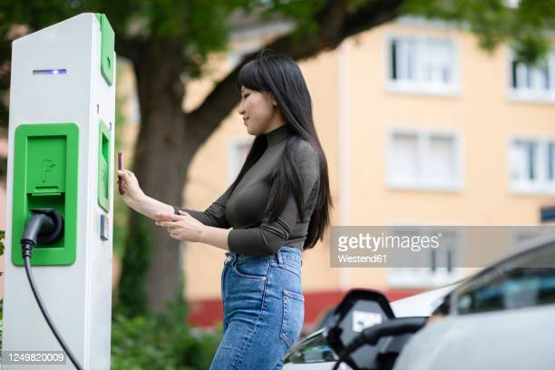carsharing, woman renting an electric car using smartphone - electric vehicle charging station stock pictures, royalty-free photos & images
