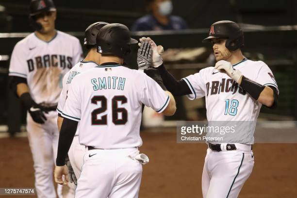 Carson Kelly of the Arizona Diamondbacks high fives Daulton Varsho and Pavin Smith after hitting a three-run home run against the Texas Rangers...
