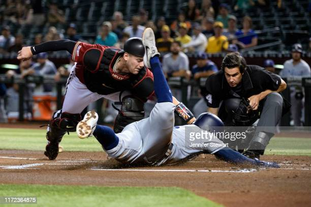Carson Kelly of the Arizona Diamondbacks makes the tag on Greg Garcia of the San Diego Padres at home plate in the first inning of the MLB game at...