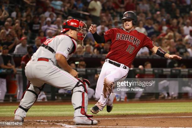 Carson Kelly of the Arizona Diamondbacks slides into home plate to score a run past catcher J.T. Realmuto of the Philadelphia Phillies during the...