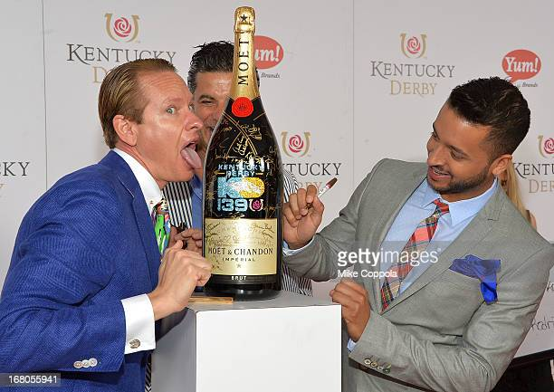 Carson Kressley and Jai Rodriguez sign the Moet Chandon 6L for the Churchill Downs Foundation during the 139th Kentucky Derby at Churchill Downs on...