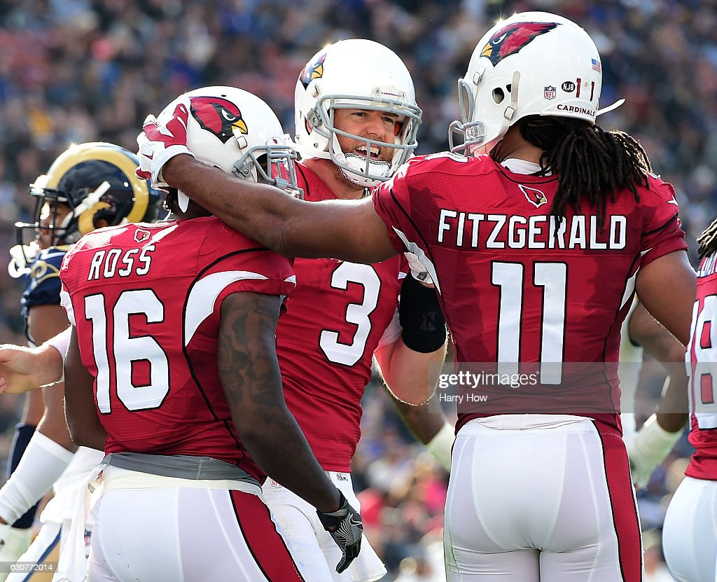 Carson Palmer #3 of the Arizona Cardinals celebrates his touchdown pass to Jeremy Ross #16 with Larry Fitzgerald #11 to take a 13-0 lead over the Los Angeles Rams during the second quarter at Los Angeles Memorial Coliseum on January 1, 2017 in Los Angeles, California.