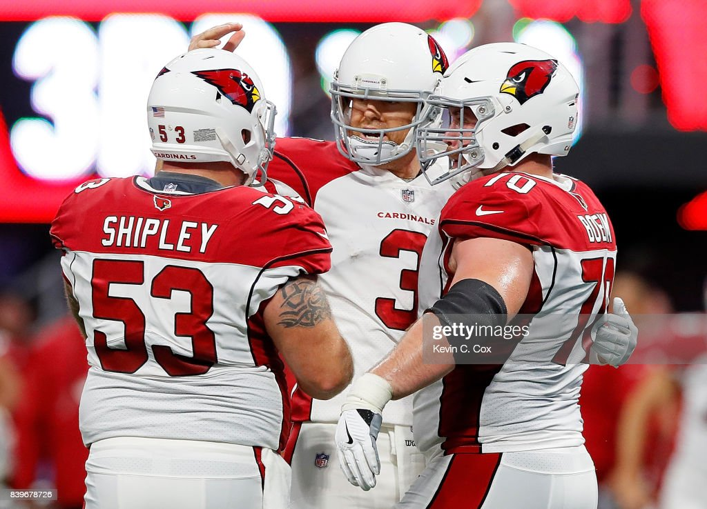 Carson Palmer #3 of the Arizona Cardinals reacts after passing for a touchdown against the Atlanta Falcons with A.Q. Shipley #53 and Evan Boehm #70 at Mercedes-Benz Stadium on August 26, 2017 in Atlanta, Georgia.