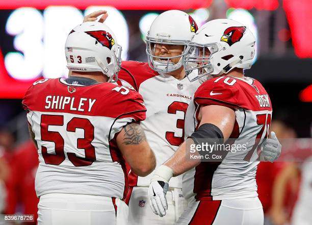 Carson Palmer of the Arizona Cardinals reacts after passing for a touchdown against the Atlanta Falcons with AQ Shipley and Evan Boehm at...