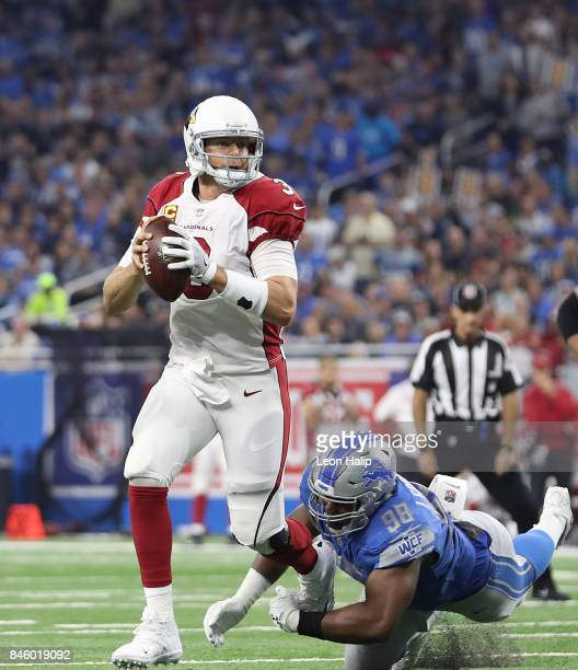 Carson Palmer of the Arizona Cardinals rolls out as Jeremiah Ledbetter of the Detroit Lions gives chase during the third quarter of the game against...