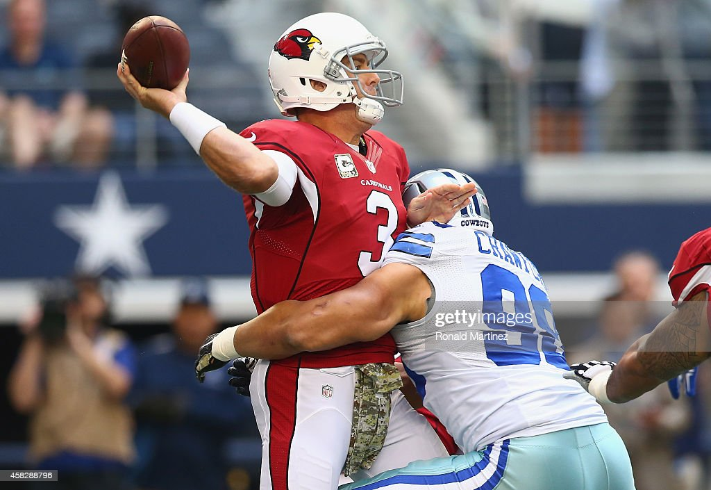Carson Palmer #3 of the Arizona Cardinals throws while hit by Tyrone Crawford #98 of the Dallas Cowboys in the first quarter at AT&T Stadium on November 2, 2014 in Arlington, Texas.