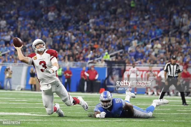 Carson Palmer of the Arizona Cardinals tries to get off a pass while being tripped by Jeremiah Ledbetter of the Detroit Lions in the first half at...