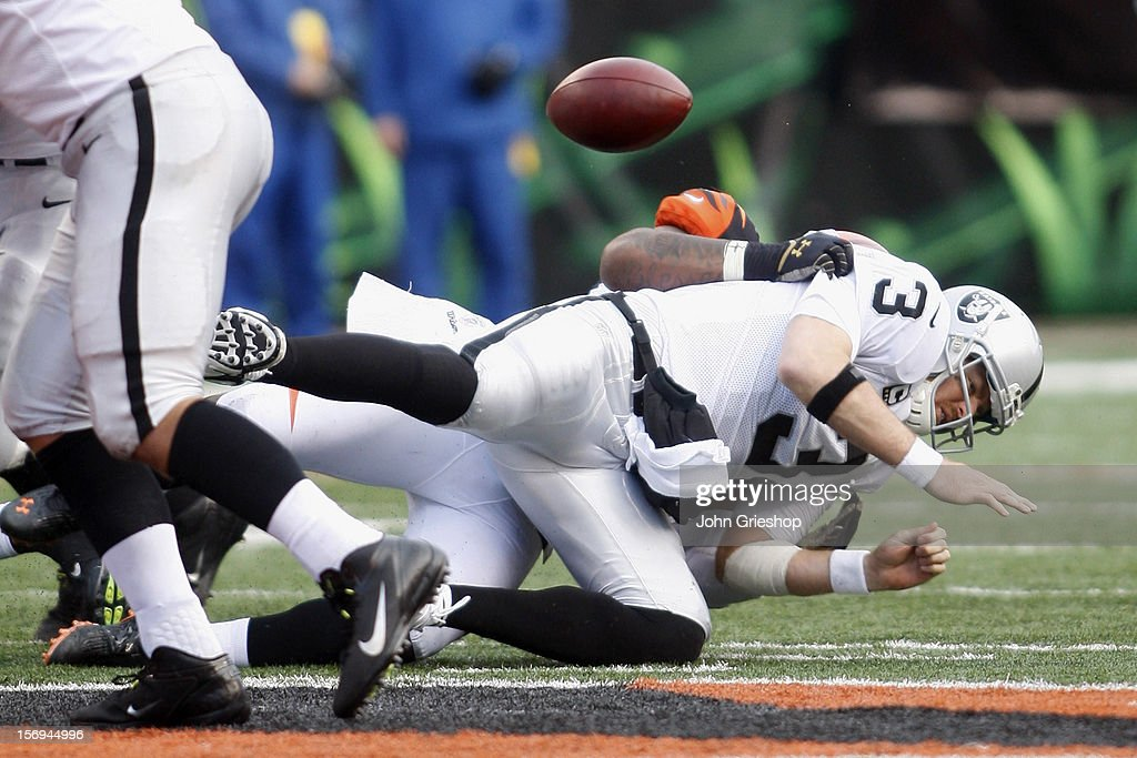 Carson Palmer #3 of the Oakland Raiders fumbles the football after being sacked during the game against the Cincinnati Bengals at Paul Brown Stadium on November 25, 2012 in Cincinnati, Ohio. The Bengals defeated the Bengals 34-10.