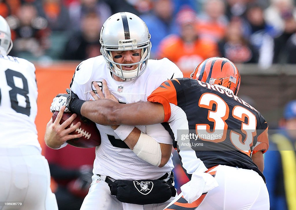 Carson Palmer #3 of the Oakland Raiders is hit by Chris Crocker #33 of the Cincinnati Bengals during the NFL game at Paul Brown Stadium on November 25, 2012 in Cincinnati, Ohio.
