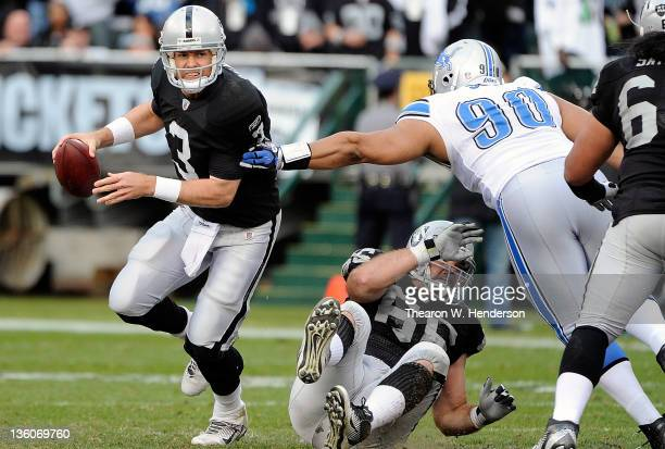 Carson Palmer of the Oakland Raiders scrambles away from Ndamukong Suh of the Detroit Lions at Oco Coliseum on December 18 2011 in Oakland California