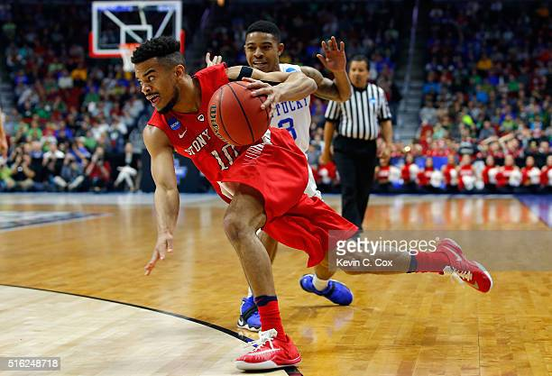 Carson Puriefoy of the Stony Brook Seawolves falls as he drives past Tyler Ulis of the Kentucky Wildcats in the first half during the first round of...