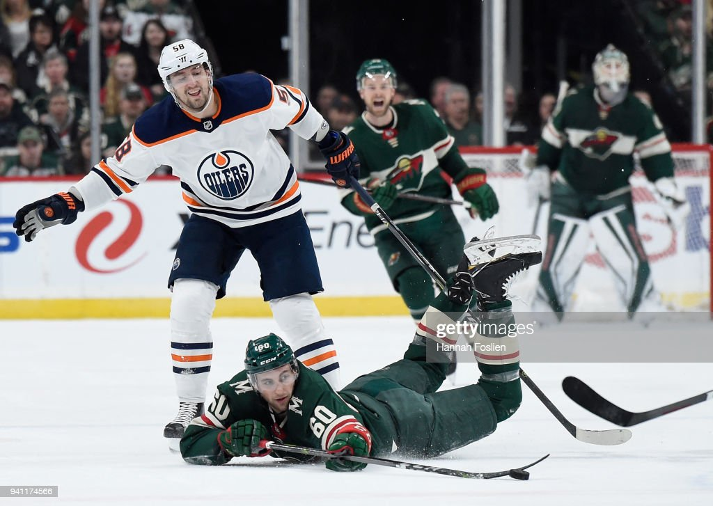 Carson Soucy #60 of the Minnesota Wild passes the puck after being tripped by Anton Slepyshev #58 of the Edmonton Oilers during the first period of the game on April 2, 2018 at Xcel Energy Center in St Paul, Minnesota. Soucy made his debut in this game.