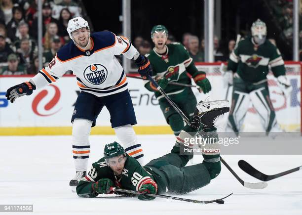 Carson Soucy of the Minnesota Wild passes the puck after being tripped by Anton Slepyshev of the Edmonton Oilers during the first period of the game...