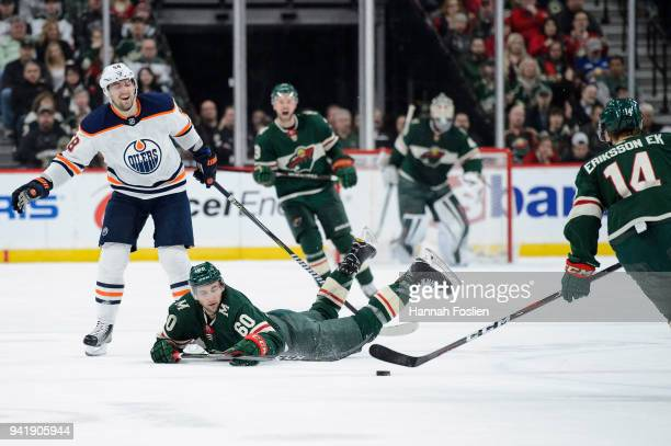 Carson Soucy of the Minnesota Wild passes the puck to teammate Joel Eriksson Ek after being tripped by Anton Slepyshev of the Edmonton Oilers during...