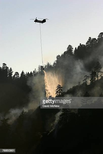 Carson Super S-61 firefighting helicopter drops water on the 24-square-mile Butler 2 Fire on September 18, 2007 near Fawnskin, California. Nearly 500...