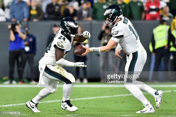Carson Wentz of the Philadelphia Eagles hands the football off to Jordan Howard of the Philadelphia Eagles against the Green Bay Packers at Lambeau...