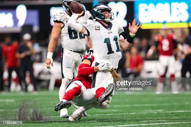 Carson Wentz of the Philadelphia Eagles is brought down while passing by Vic Beasley of the Atlanta Falcons during the second half of a game at...