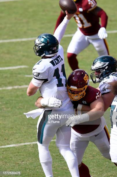 Carson Wentz of the Philadelphia Eagles is hit by Matthew Ioannidis of the Washington Football Team at FedExField on September 13, 2020 in Landover,...