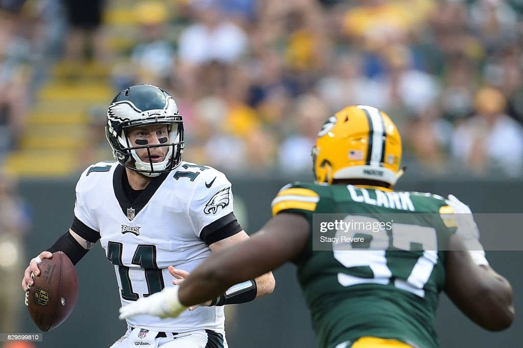 Carson Wentz #11 of the Philadelphia Eagles is pursued by Kenny Clark #97 of the Green Bay Packers during the first quarter of a preseason game at Lambeau Field on August 10, 2017 in Green Bay, Wisconsin.