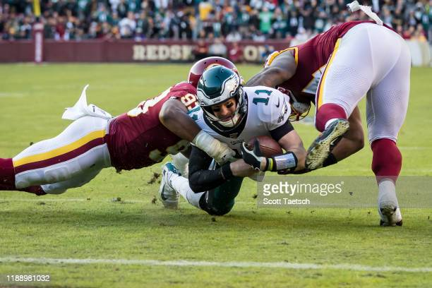 Carson Wentz of the Philadelphia Eagles is tackled by Jonathan Allen of the Washington Redskins during the second half at FedExField on December 15,...