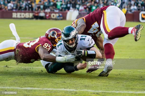 Carson Wentz of the Philadelphia Eagles is tackled by Jonathan Allen and Daron Payne of the Washington Redskins during the second half at FedExField...