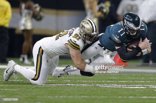 Carson Wentz of the Philadelphia Eagles is tackled by Trey Hendrickson of the New Orleans Saints during the first half at the MercedesBenz Superdome...