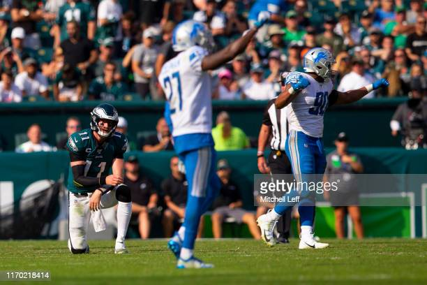 Carson Wentz of the Philadelphia Eagles looks on as Justin Coleman and Trey Flowers of the Detroit Lions celebrate a turnover on downs by the Eagles...
