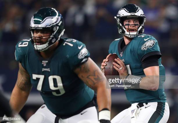 Carson Wentz of the Philadelphia Eagles looks to pass as Brandon Brooks blocks during the first half against the Dallas Cowboys in the game at ATT...