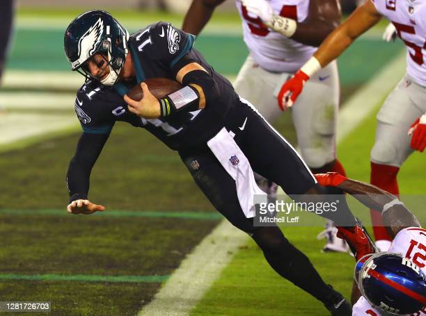 Carson Wentz of the Philadelphia Eagles scores a touchdown against Jabrill Peppers of the New York Giants during the first quarter at Lincoln...