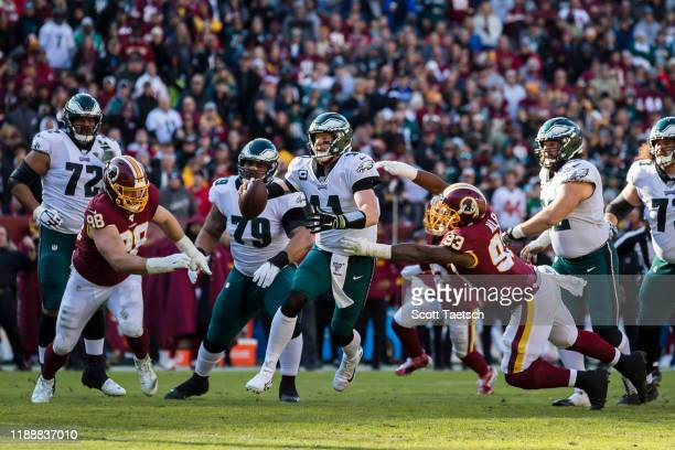 Carson Wentz of the Philadelphia Eagles scrambles under pressure by Jonathan Allen of the Washington Redskins during the first half at FedExField on...