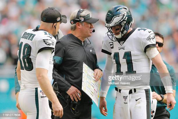 Carson Wentz of the Philadelphia Eagles talks with head coach Doug Pederson and Josh McCown against the Miami Dolphins during the second quarter at...