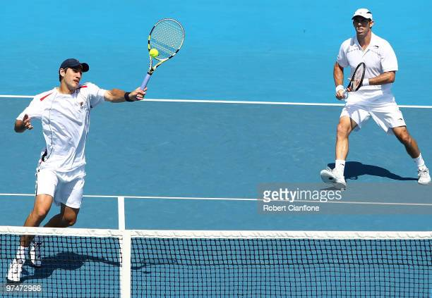 Carsten Ball of Australia returns a shot as Paul Hanley looks on during their doubles match against TsungHua Yang and ChuHuan Yi of Chinese Taipei...