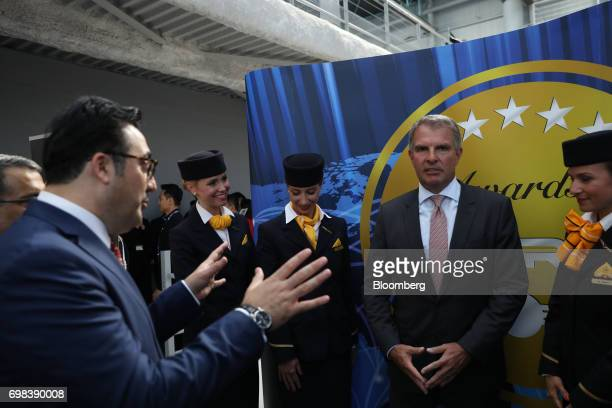 Carsten Spohr chief executive officer of Deutsche Lufthansa AG second right looks on as Ilker Ayci chairman of Turkish Airlines left gestures during...