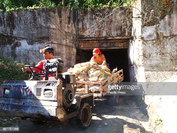 Cart coming out of the gold mining tunnel with sacks of rocks with possible gold minerals in it.