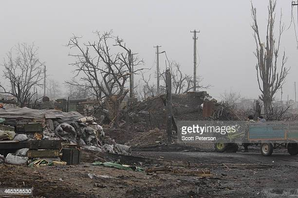 A cart drives past checkpoint trenches as Ukrainians cope with extensive destruction of war after a midFebruary battle that left control of...