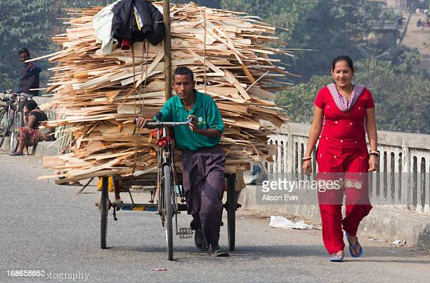 Cart full to the brim with plywood strips is pushed across the bridge between the India and Nepal border by bicycle. This is how most loads are...