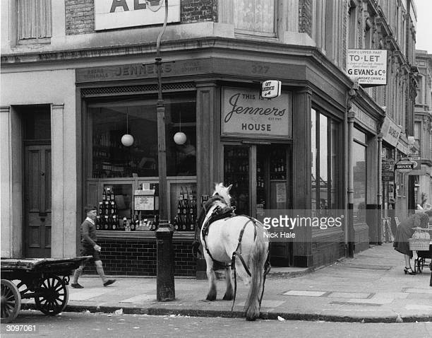 A cart horse waits on the pavement outside Jenners an off licence in Portobello Road London